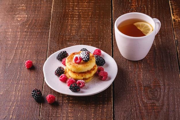 Crêpes au fromage cottage beignets de caillé dessert avec framboises et mûres dans une assiette près de tasse de thé chaud avec tranche de citron sur fond de bois brun foncé vue d'angle