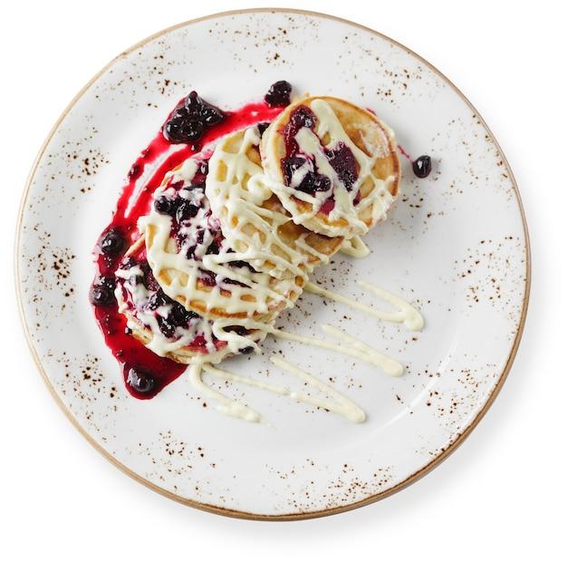 Crêpes au fromage cottage ou beignets de lait caillé décorés de bleuets dans une assiette sur la vue de dessus de table blanche.