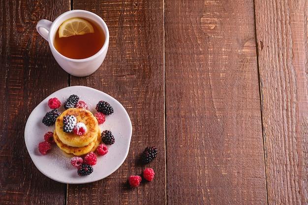 Crêpes au fromage cottage, beignets de lait caillé dessert avec des baies de framboises et de mûres dans une assiette près de tasse de thé chaud avec tranche de citron sur fond en bois brun foncé, espace de copie de vue d'angle