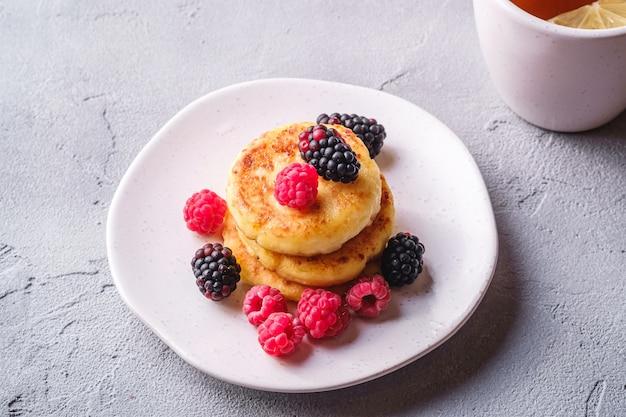 Crêpes au fromage cottage, beignets de lait caillé dessert avec framboises et mûres dans une assiette près d'une tasse de thé chaud