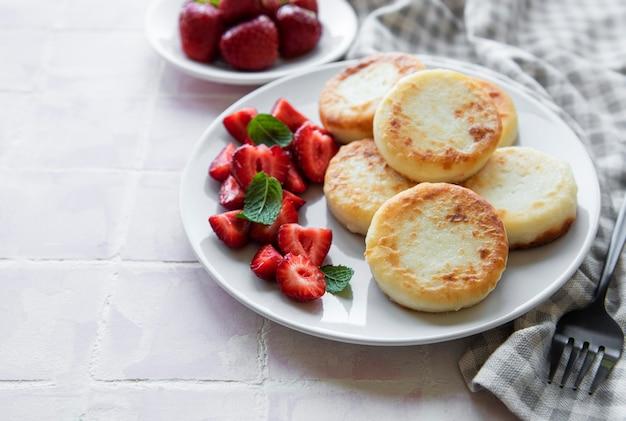 Crêpes au fromage cottage beignets de ricotta sur plaque en céramique avec fraise fraîche