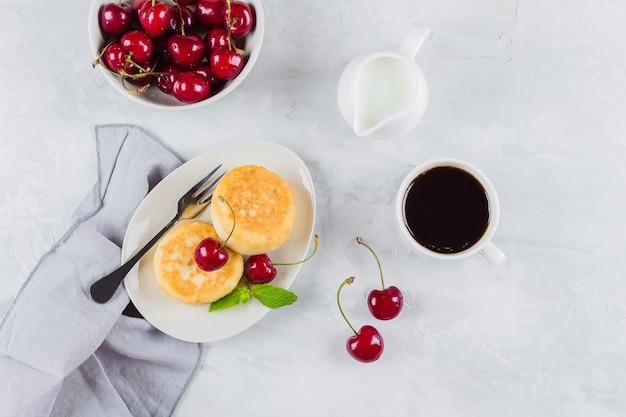 Crêpes au fromage cottage avec cerises et baies, tasse de café noir, lait et bol