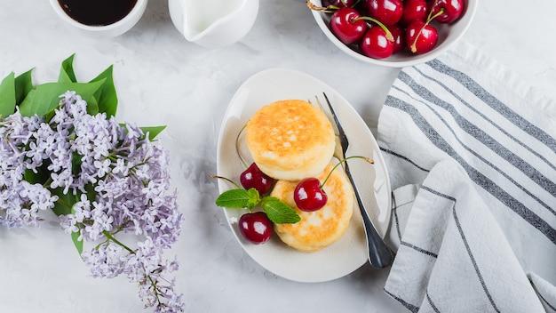 Crêpes au fromage cottage avec des cerises et une tasse de café noir