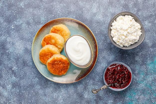 Crêpes au fromage cottage avec de la confiture de framboise.syrniki russe ou sirniki, beignets au fromage cottage ou crêpes avec un bol de fromage cottage frais fait maison sur gris foncé