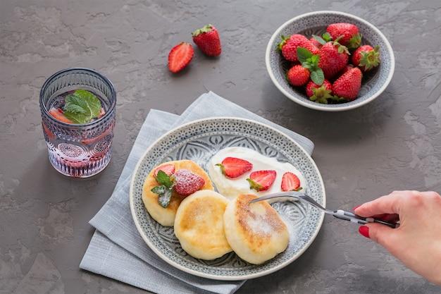 Crêpes au fromage cottage avec de la crème sure et des fraises pour le petit déjeuner ou le déjeuner sur fond gris.