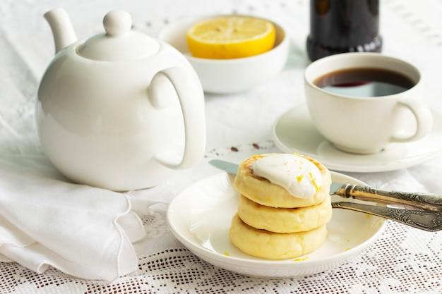 Crêpes au fromage cottage avec crème sure et zeste de citron, servies avec du thé. mise au point sélective.