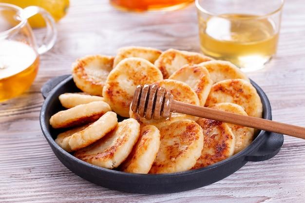Crêpes au fromage cottage avec du miel sur une assiette sur fond de bois. petit déjeuner