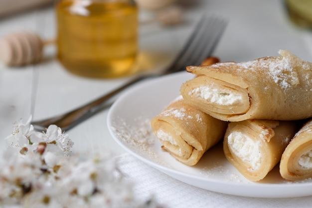 Crêpes au fromage cottage sur un fond en bois blanc. tourné avec du miel, des graines de tournesol, de la farine et des œufs. un petit déjeuner traditionnel.