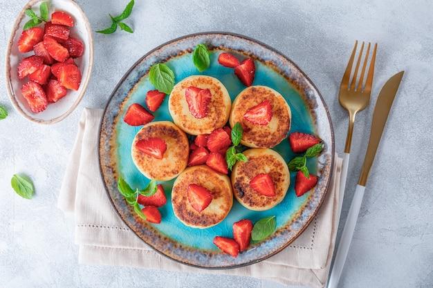 Crêpes au fromage cottage avec fraises et menthe sur une plaque bleue vue de dessus fond gris clair