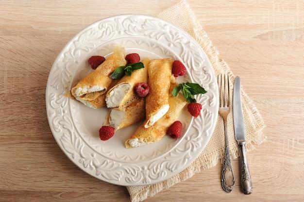 Crêpes au fromage cottage et framboises sur une assiette