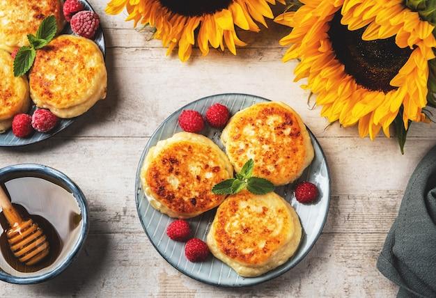 Crêpes au fromage cottage avec framboises et feuilles de menthe sur une assiette.