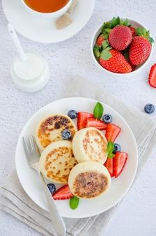 Crêpes au fromage cottage frites ou syrniki avec des baies fraîches sur une plaque blanche avec de la crème sure. sans gluten. petit déjeuner traditionnel de cuisine ukrainienne et russe.