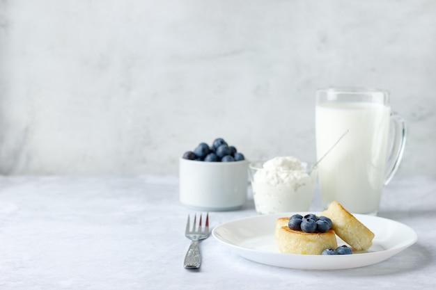 Crêpes au fromage cottage avec myrtille, crème sure et verre de lait sur fond de pierre. petit-déjeuner sain. copiez l'espace pour votre texte.