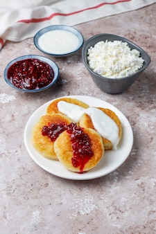 Crêpes au fromage cottage.srniki russe ou sirniki, beignets au fromage cottage ou crêpes avec un bol de fromage cottage frais fait maison