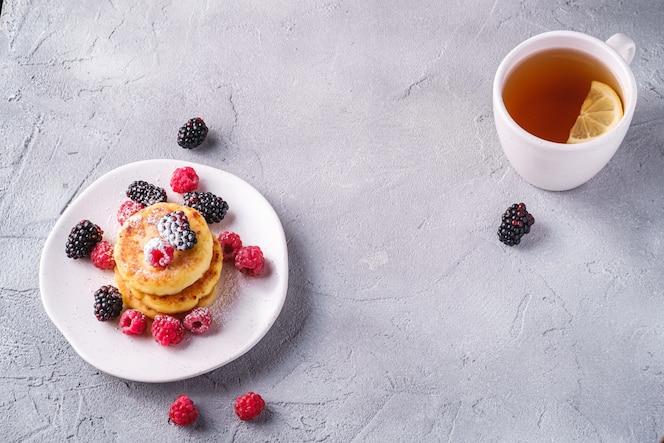 crêpes au fromage cottage et sucre en poudre avec des baies dans une assiette près d'une tasse de thé chaud avec une tranche de citron