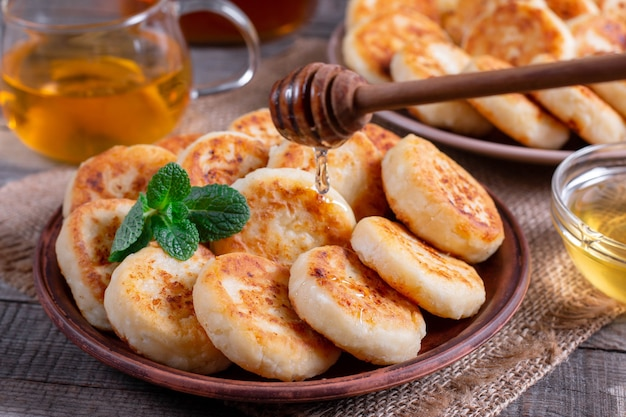 Crêpes au fromage cottage, syrniki au miel sur une assiette sur fond de bois. petit déjeuner