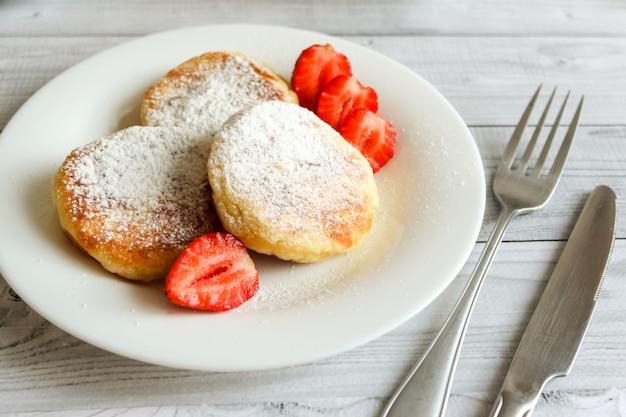 Crêpes au fromage cottage ou syrniki aux fraises sur plaque blanche.
