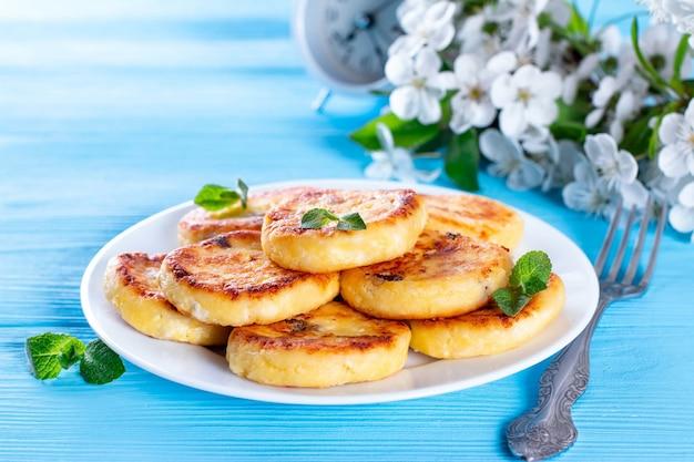 Crêpes au fromage cottage ou syrniki à la menthe sur fond bleu. petit-déjeuner ou déjeuner sain