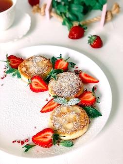 Crêpes au fromage faites maison avec des fraises sur une plaque blanche sur un fond texturé blanc