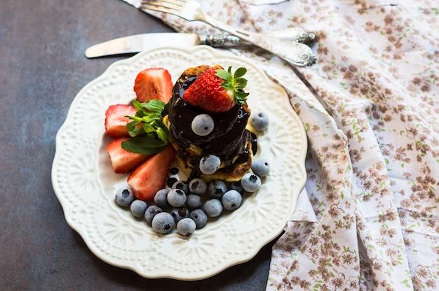 Crêpes au fromage avec des fraises et des bleuets recouverts de chocolat pour le petit déjeuner