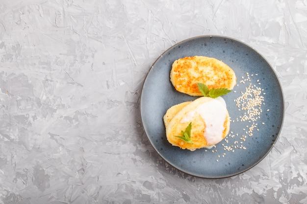 Crêpes au fromage sur une plaque en céramique bleue avec de la sauce au lait sur un béton gris.