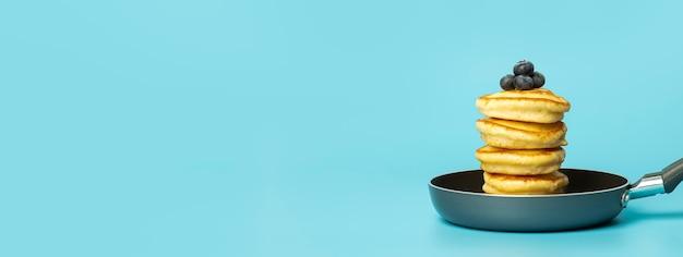 Crêpes aux baies sur fond de bannière bleue délicieuses crêpes luxuriantes aux myrtilles et au sirop...