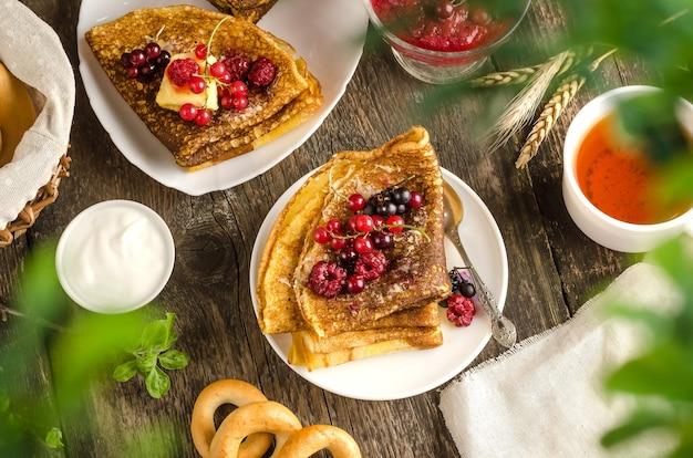 Crêpes aux baies sur un fond en bois avec une tasse de thé, une sauce et des feuilles au premier plan