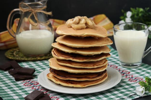 Crêpes aux bananes sur une assiette, derrière est une cruche et un verre de lait