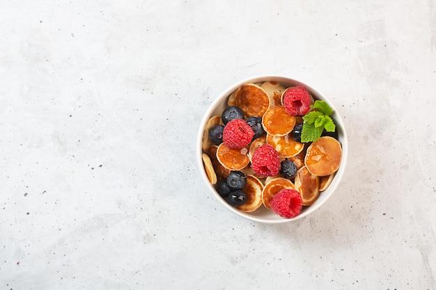 Crêpes aux bleuets, framboises, menthe et miel pour un petit déjeuner, vue de dessus avec copie espace