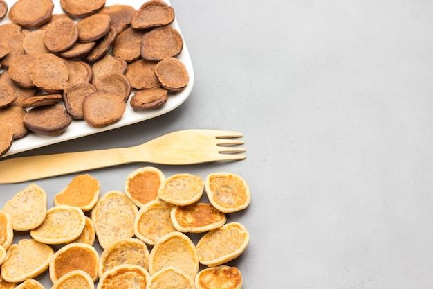 Crêpes aux céréales sur fond gris et fourchette en bois. mise à plat. copier l'espace