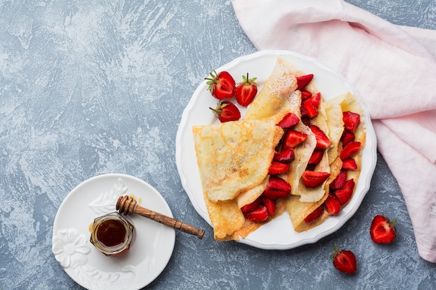 Crêpes aux fraises fraîches et au miel sur fond de béton gris. vue de dessus.