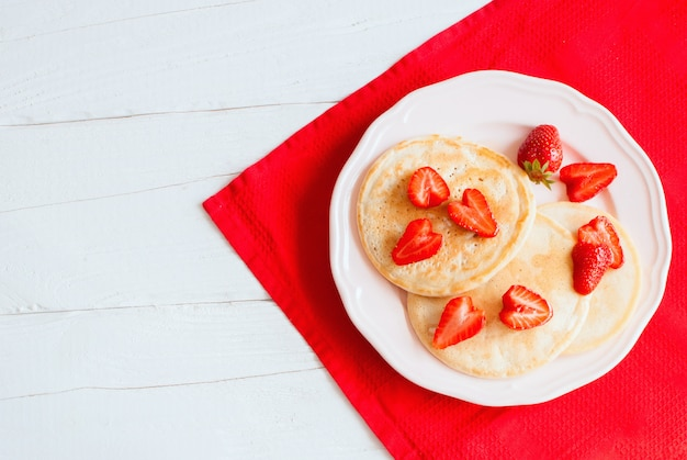 Crêpes aux fraises sur une table en bois blanc