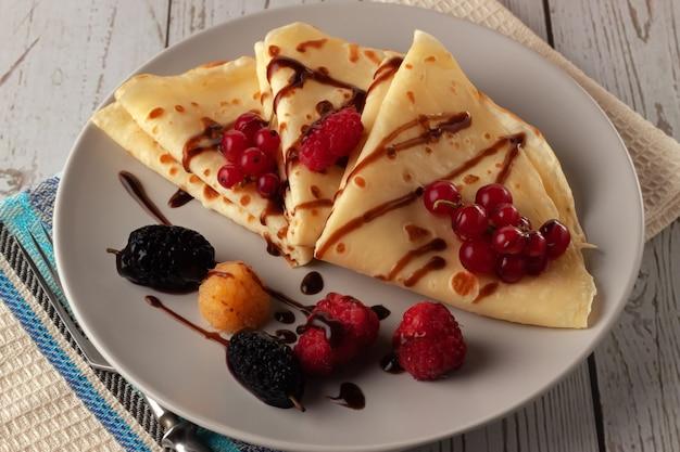 Crêpes aux framboises, groseilles et chocolat sur une assiette, décorées d'une feuille de menthe