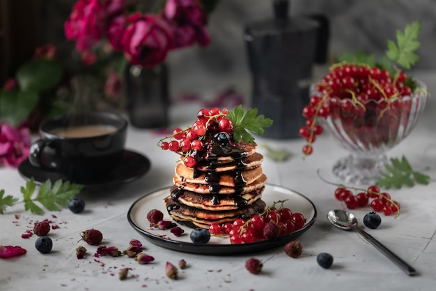 Crêpes aux fruits rouges et chocolat sur fond clair avec un bouquet de roses rouges. photo sombre.