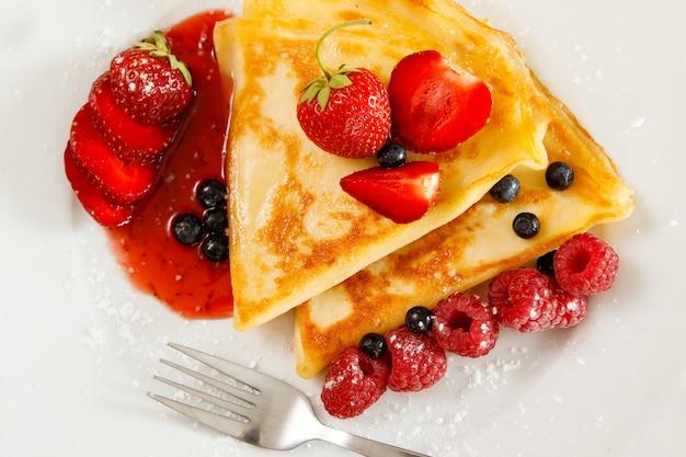 Crêpes aux fruits rouges et sucre en poudre