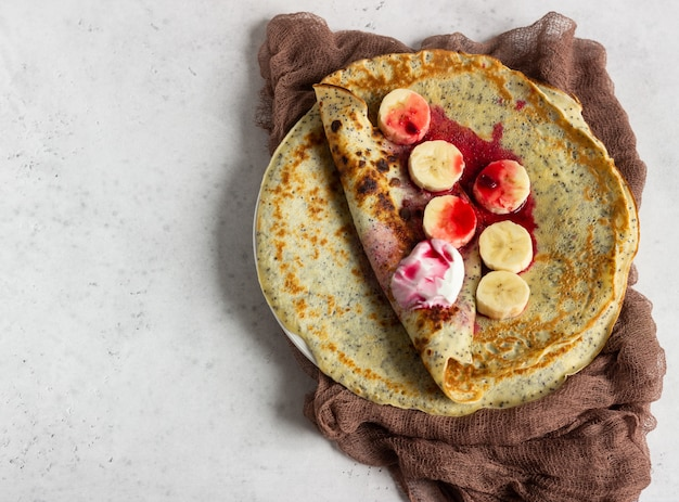 Crêpes aux graines de pavot avec sauce au yogourt naturel, aux bananes et aux cerises avec épices