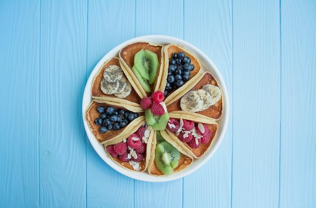 Crêpes avec des baies fraîches sur un bois bleu. crêpes aux fruits. petit déjeuner estival fait maison.
