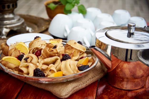 Des crêpes avec des baies fraîches dans une assiette en verre reposent sur une table en bois avec un samovar et des tasses à l'air frais.