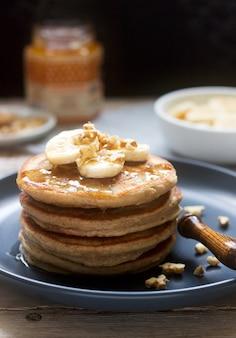 Crêpes à la banane, aux noix et au miel, servies avec du thé. style rustique.