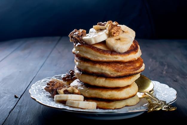 Crêpes à la banane, noix, miel et verre de café sur fond noir