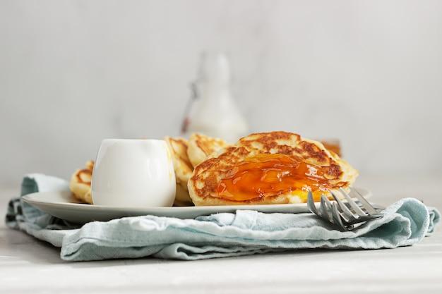 Crêpes ou beignets américains à la confiture d'orange et bouteille de lait