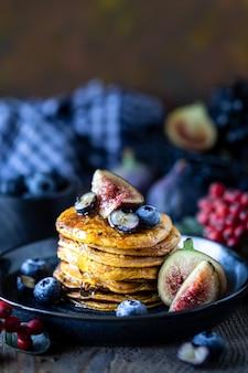 Crêpes à la citrouille avec sirop ou miel, graines de lin, figues, bleuets dans une assiette sombre sur la table, mise au point sélective, espace copie
