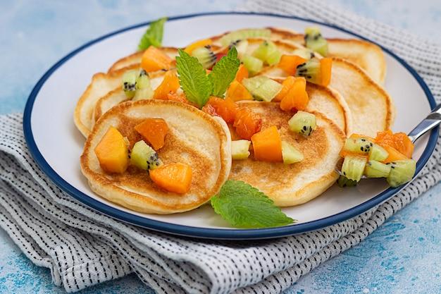 Crêpes classiques avec abricot, kiwi et menthe sur plaque en céramique