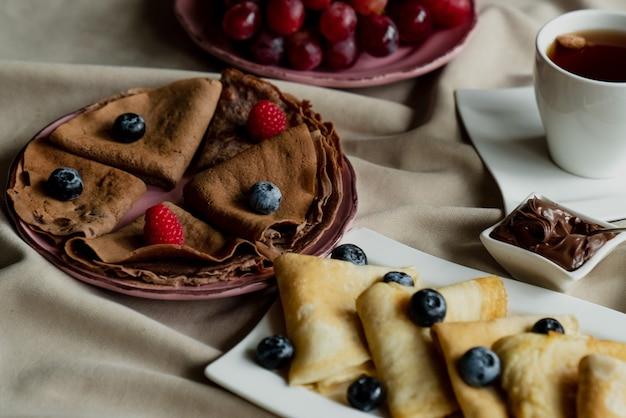 Crêpes classiques et au chocolat avec baies et fruits pour le petit déjeuner, chocolat, thé,
