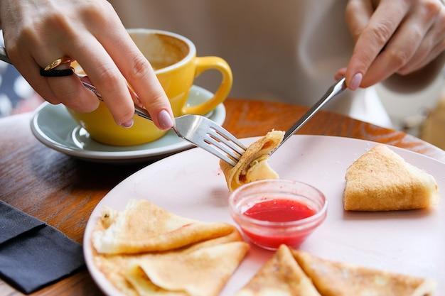 Crêpes à la confiture de baies, cappuccino. fourchette et couteau dans les mains d'une femme.