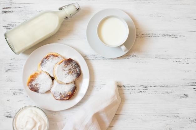 Crêpes cottage cheese. cheesecakes. syrniki ou sirniki. petit-déjeuner sain. plats blancs. bouteille de lait. une tasse de lait. yaourt ou crème sure. fond blanc. vue de dessus. espace pour le texte