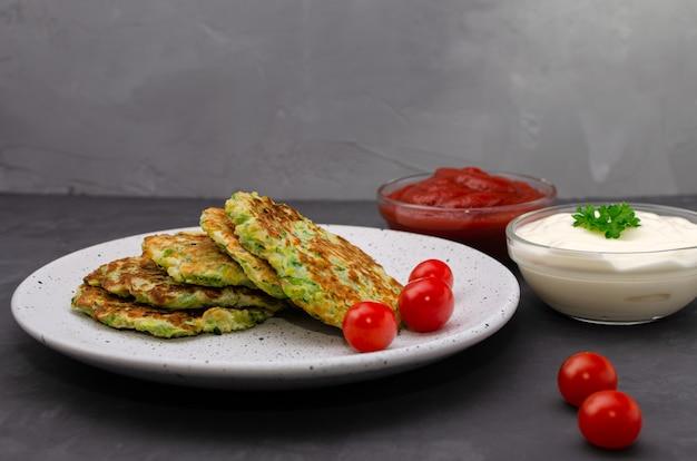 Crêpes de courgettes aux légumes servies avec du yaourt et de la sauce tomate