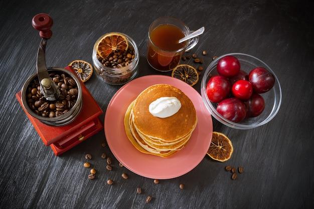 Crêpes à la crème sure dans une assiette rose, café dans une tasse en verre transparent, grains de café dans un broyeur vintage, prunes rouges dans un bol transparent, tranches de citron séchées.