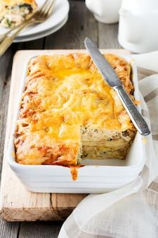Crêpes cuites au four avec poulet, champignons, épinards et fromage sous forme de céramique blanche.