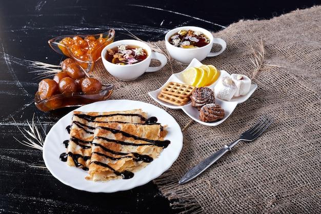 Crêpes dans une assiette blanche avec du sirop de chocolat et du thé.